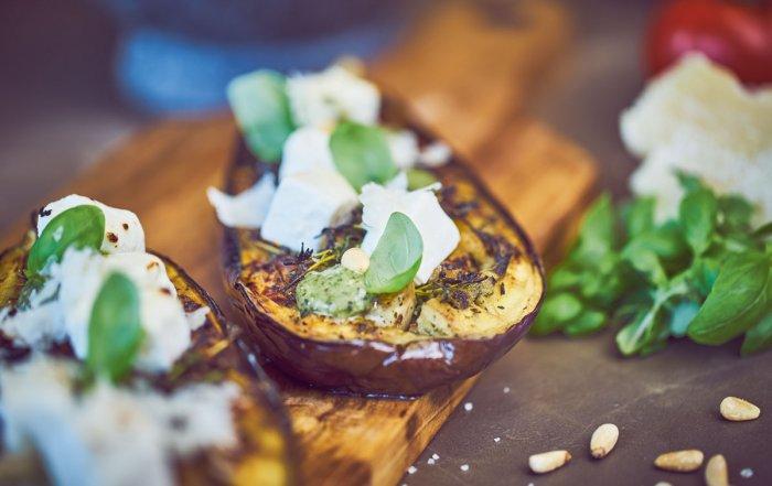 Lecker gegrillte Auberginen-Schiffchen mit leicht geschmolzenem Fetakäse und Basilikumblättern auf einem Holzbrett wecken die Lust auf die Grill-Saison mit vegetraischen Grillrezepten.
