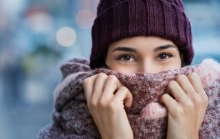 Eine junge Frau mit dunkelroter Wintermützehält sich einen dicken, rötlichen Schal ins Gesicht.
