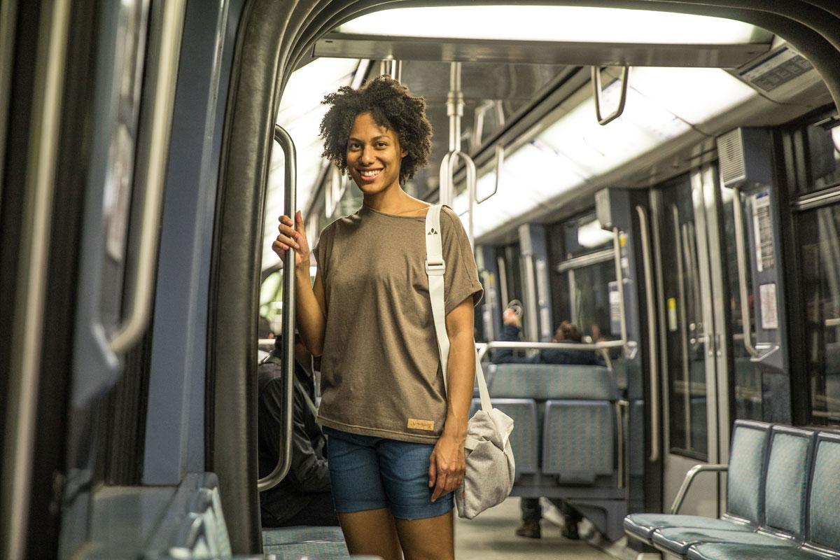 Junge Frau mit Vaude Tasche in der U-Bahn