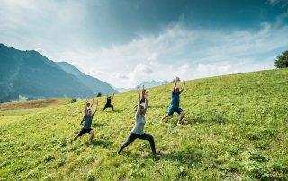 Eine kleine Gruppe Menschen in einer Yoga-Pose auf einer Wiese beim Naturhotel Chess Valisa