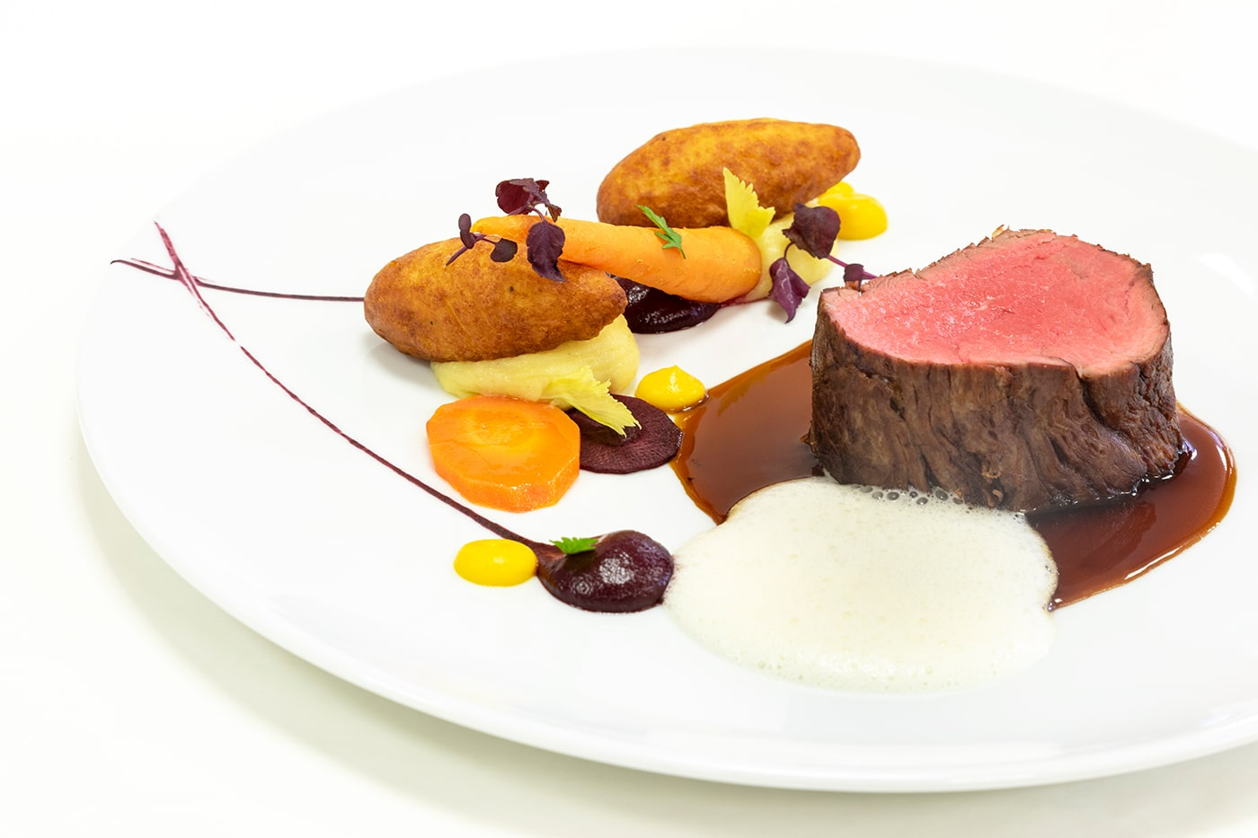 Ein Teller mit rosagebratenem Fleisch und Beilagen aufwendig garniert