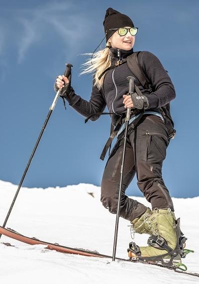 Auf einer Schneepiste steht eine blonde Skifahrerin, mit funktionaler Skikleidung von Woolpower bekleidet.