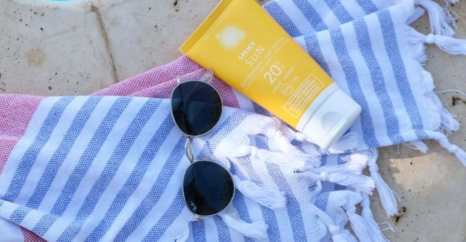Die mineralbasierte Sonnencreme mit LSF 20 von Speick Sun liegt in ihrer gelben Tube am Rand eines türkisblauen Swimmingpools auf einem blau-weiß gestrieften Strandtuch mit Fransen neben einer Sonnenbrille.