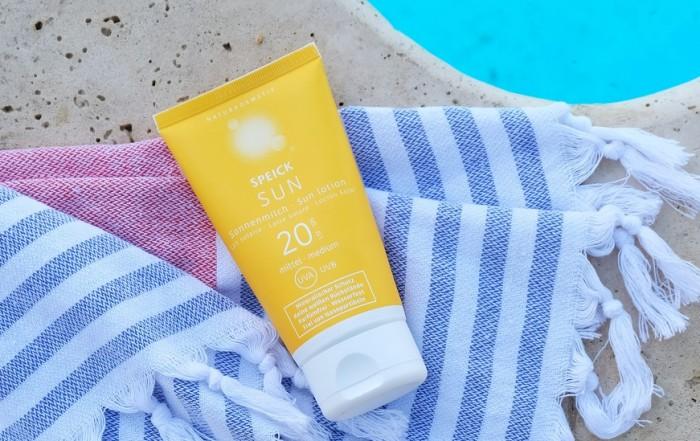 Die neue natürliche Sonnencreme von SPEICK erkennt man am gelben Produktdesign, hier zu sehen auf einem blau-weiß gestreiften Hamam-Tuch mit weißen Fransen an einem azurblauen Swimmingpool.