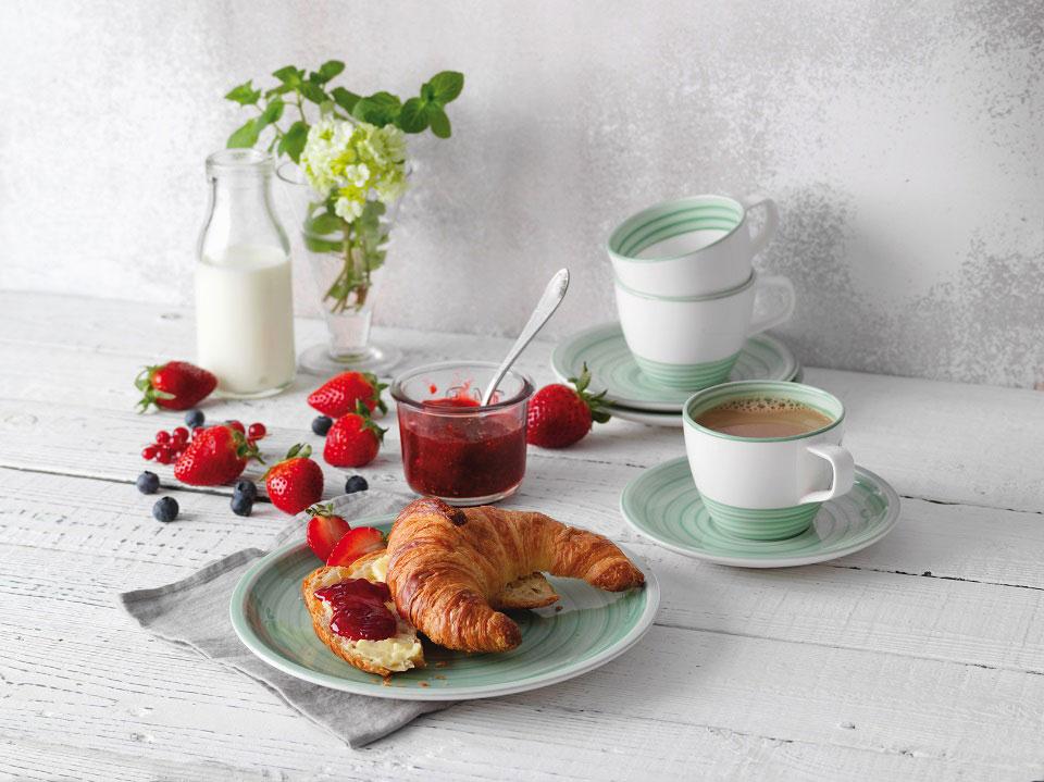 Auf Geschirr von Villeroy & Boch-Kollektion Artesano Nature Vert ist ein Buttercroissant aufgeschnitten und bereits mit selbstgekochter Konfitüre beschmiert.