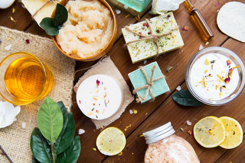 Handgeschöpfte Seifen, Peelings und Badesalze auf einem dunklen Holztisch symbolisieren die Vielfalt und Auswahl, die es heutzutage bei Naturkosmetik gibt.