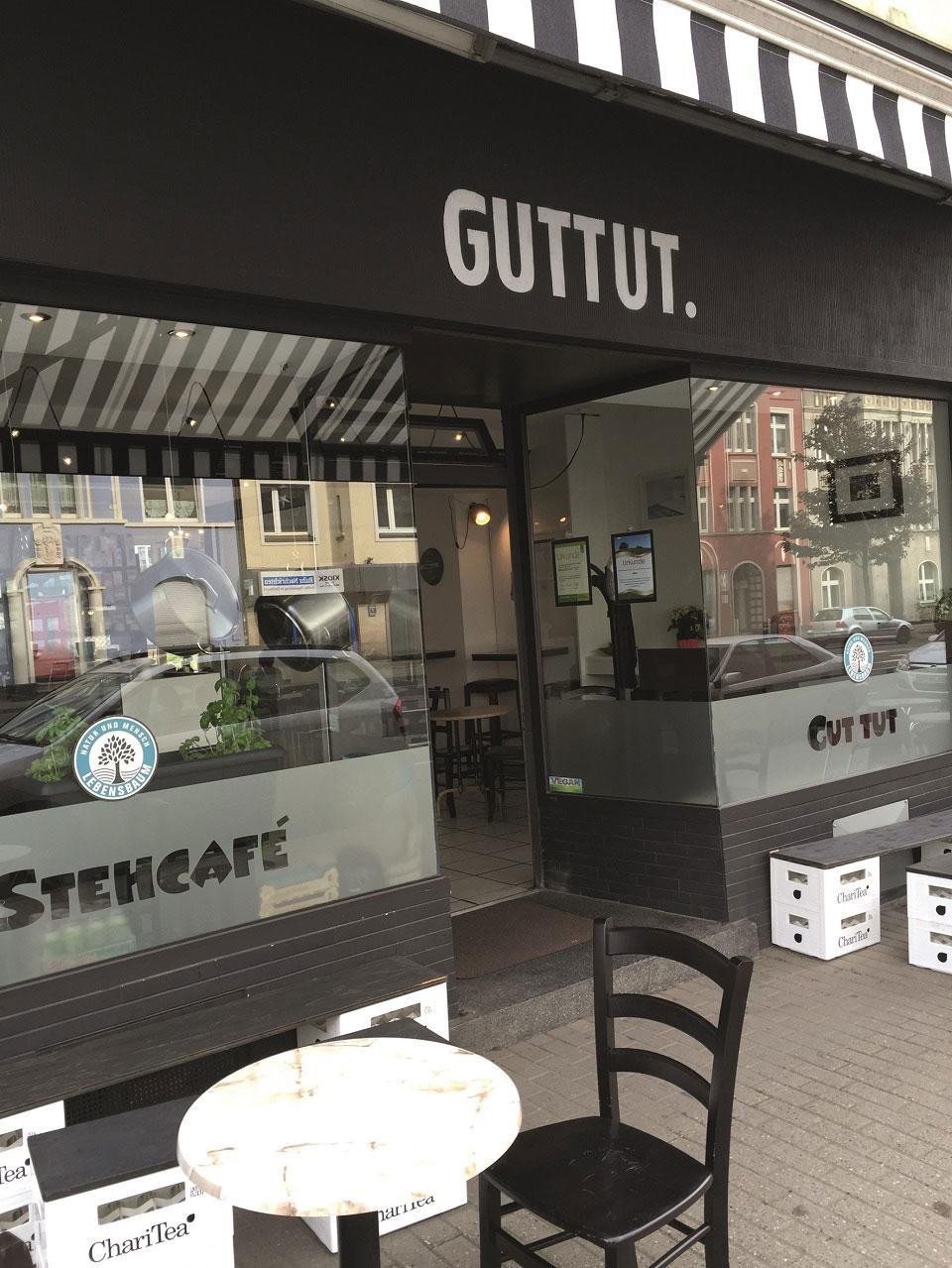 Vor dem Restaurant Guttut in Dortmund laden schwarze und weiße Möbel sowie Hocker aus Getränkekisten zum Schlemmen in der Sonne ein.