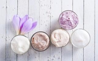 Verschiedene Cremes, Schampoos und Peelings verteilt auf fünf Tiegel, arrangiert mit einer violetten Krokusblüte. Wir nutzen Pflegeprodukte, um uns etwas Gutes zu tun. Doch nicht alle Inhaltsstoffe in Kosemtika sind bedenkenlos für unsere Gesundheit.
