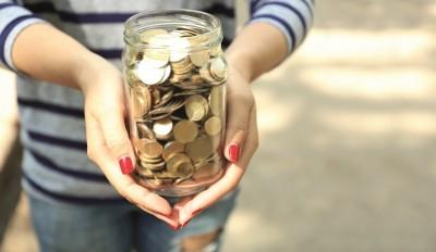 Schon ein bisschen Kleingeld in einem Glas kann helfen ein Crowdfunding-Projekt zu unterstützen und damit die Welt zu verbessern. Hier wird das Glas von einer jungen Frau in einem Ringel Shirt und rot lackierten Fingernägeln symbolisch gehalten.