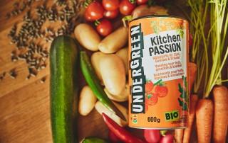 Die flachen Düngerpallets von Undergreen liegen in ihrer orangenen Verpackung auf verschiedenen Gemüsesorten wie Zucchini, Kartoffeln, Möhren, Tomaten sowie grünen und roten Paprikaschoten.