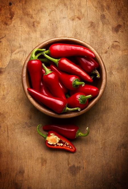 In einer Schüssel lieben schmale, rote Schoten im Ganzen, vor der Schüssel die beiden Hälften einer aufgeschnittenen Schote, die vermutlich ziemlich scharf sind, da sie scheinbar zu den Chilifrüchten zählen.