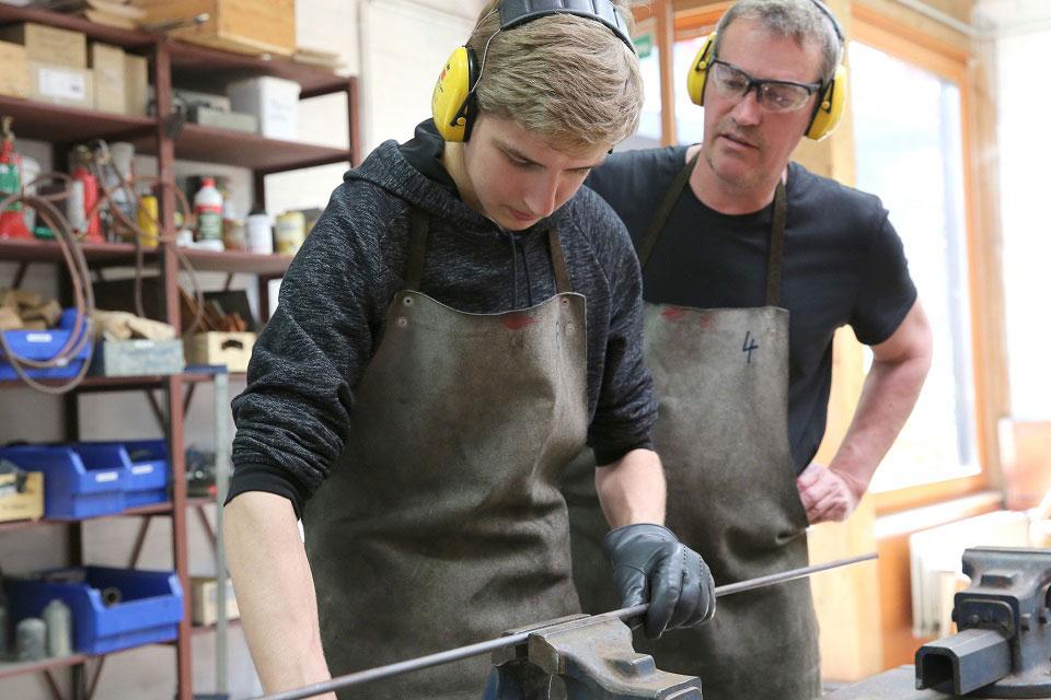 An der Waldorfschule wird ein Schüler in Schutzkleidung und mit gelbem Gehörschutz von einem Lehrer in gleicher Arbeitsmontur an das Metallhandwerk herangeführt.