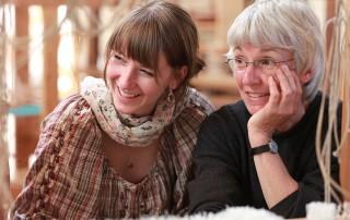 Zwei weibliche Lehrfräte, eine jüngere Waldoflehrerin und eine etwas ältere Pädagogin, haben betrachten mit einem Lächeln die Waldorfschüler und das Geschehen während des Unterrichts.