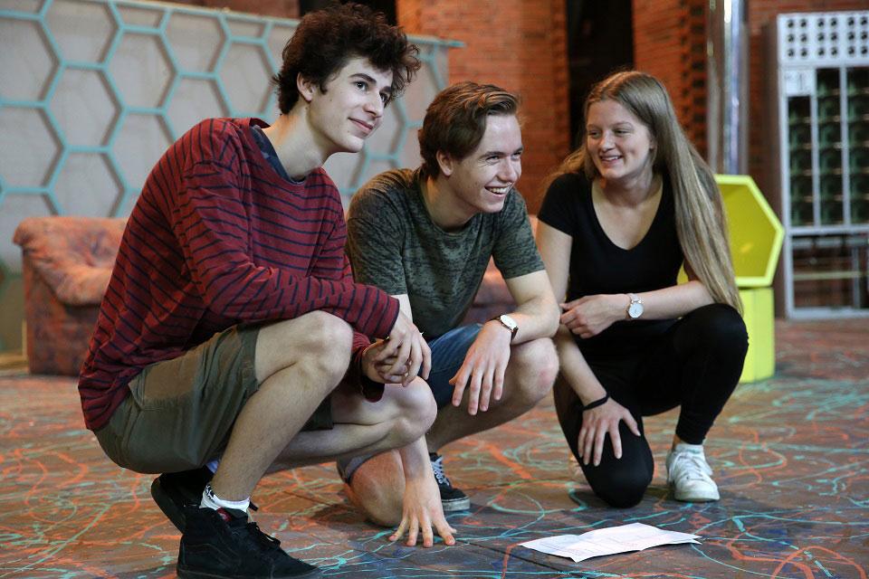 Drei Waldorfschüler knien am Boden und arbeiten gemeinsam als Team.