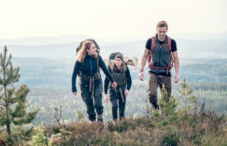 Drei junge Wanderer besteigen einen bewachsenen Hügel in einer Bergregion und tragen für ihren Outdoortrip Funktionskleidung von Woolpower.