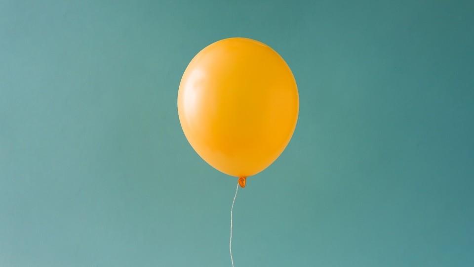 Ein gelber Ballon schwebt vor einem grün-blauen Hintergrund