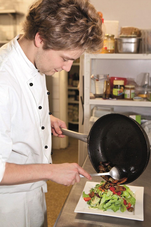 Ein junger Koch richtet in der Küche des Zurück zum Glück ein Gericht in zertifizierter Bioqualität an.