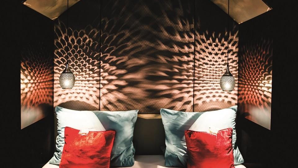 Die Lampen im Schlafbereich des Chalets werfen kleine Hängeleuchten Schattenspiele, die an eine Diskokugel erinnern, an die rostrote Wand.