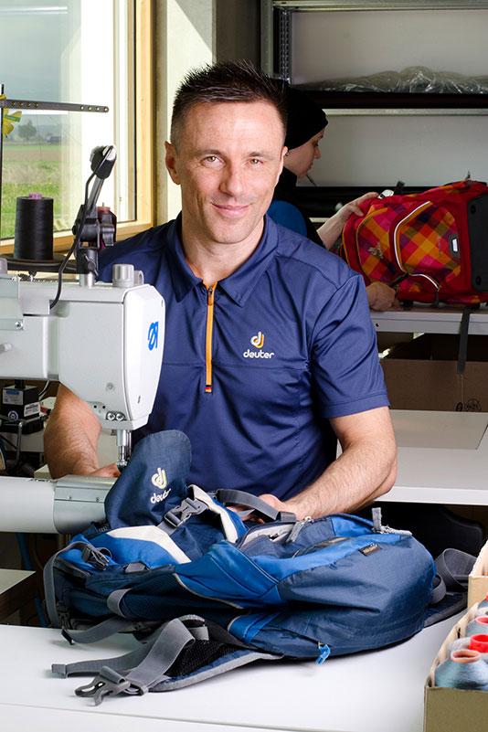 Deuter Nachhaltigkeit: Ein Mann vom Reparaturservice sitzt an einer Nähmschine