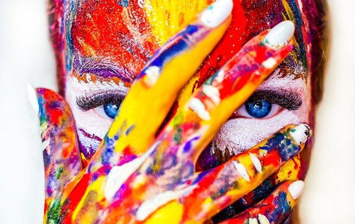 Duftstoffe in Kosmetik können Hautreizungen verursachen, die hier als bunte Farbe im Gesicht dargestellt wird.