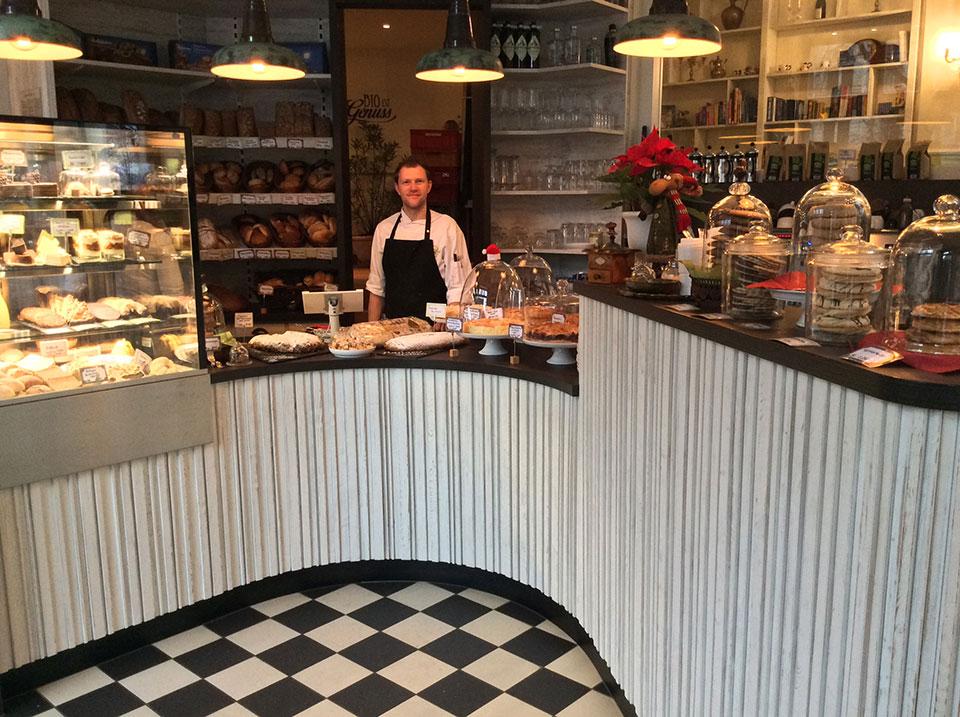 Im modernen, schwarz-weiß gestalteten Eingangsbereich von Heller's Kuchenglocke in Dresden wird der Gast von freundlichem Personal hinter sowie einer leckeren Auswahl an Biokuchen und anderen Leckereien in Bioqualität auf dem Tresen begrüßt.