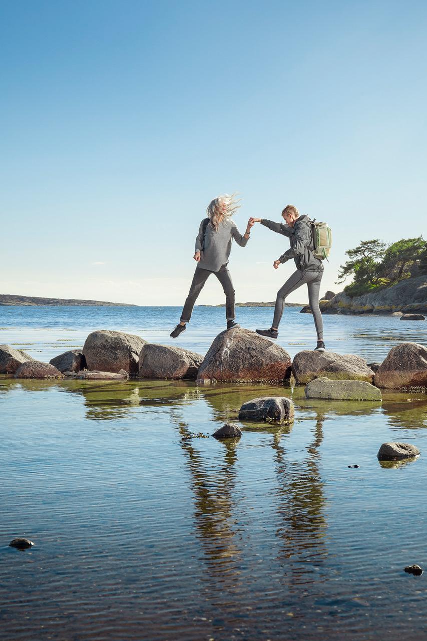 Nachhaltige Schuhe - Ein Paar überquert einen Fluss auf Felsen mit festem Schuhwerk.