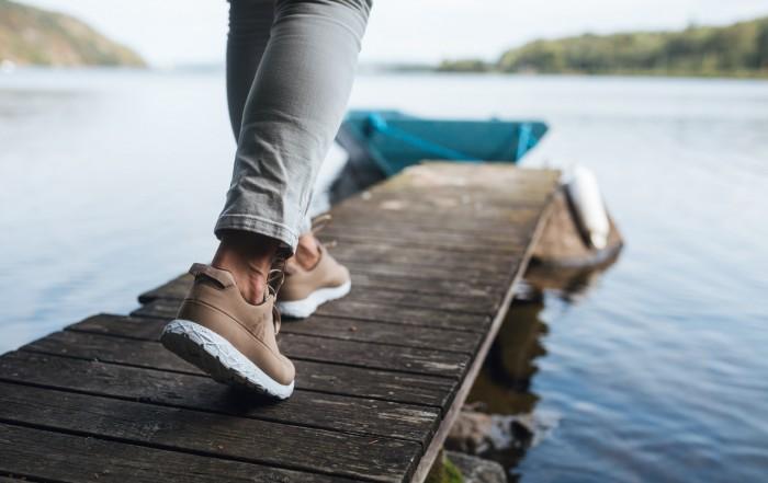 Nachhaltige Schuhe - Damensneaker auf einem Steg am Wasser