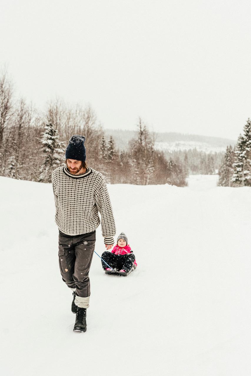 Nachhaltige Schuhe - Vater zieht sein Kind auf Schlitten den Berg hinauf