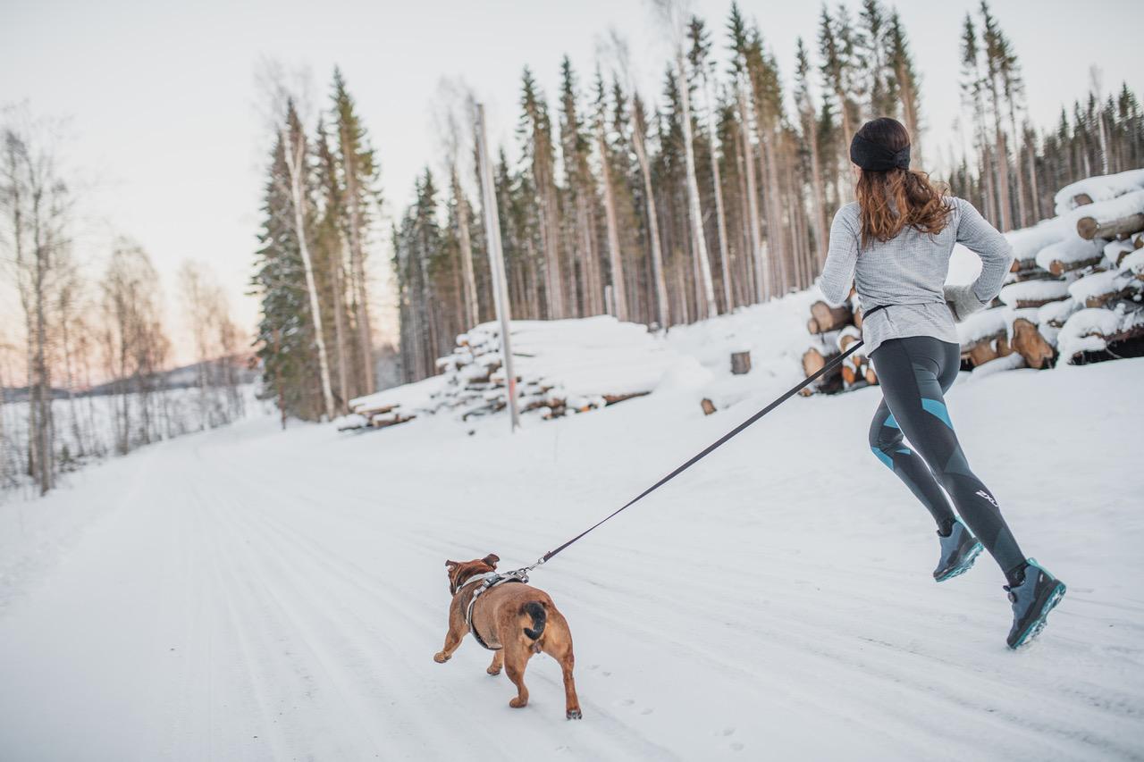 Nachhaltige Schuhe - Junge Frau joggt im Winter mit ihrem Hund