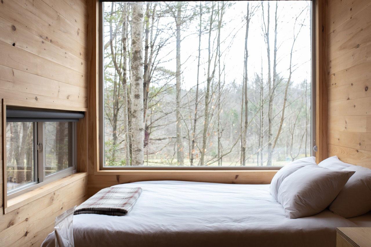 Nachhaltiges Schlafzimmer aus holz mit großem Fenster und Blick auf Bäume