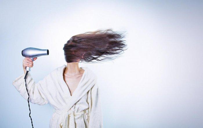 Frau föhnt ihre Haare nach der Umstellung auf Naturkosmetik-Shampoo