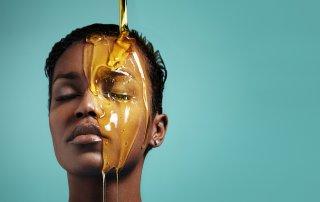 Honig fließt über das Gesicht einer Frau Symbolbild