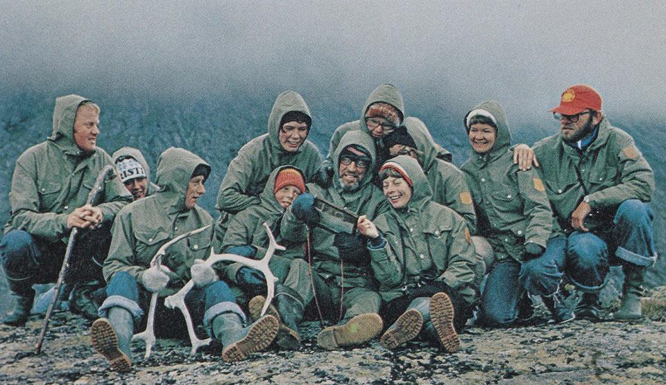 Rund 15 Personen tragen die beliebte Greenland Jacket von Fjällräven und posieren für ein Gruppenbild in freier Natur, das etwa in den 1970er Jahren aufgenommen wurde.