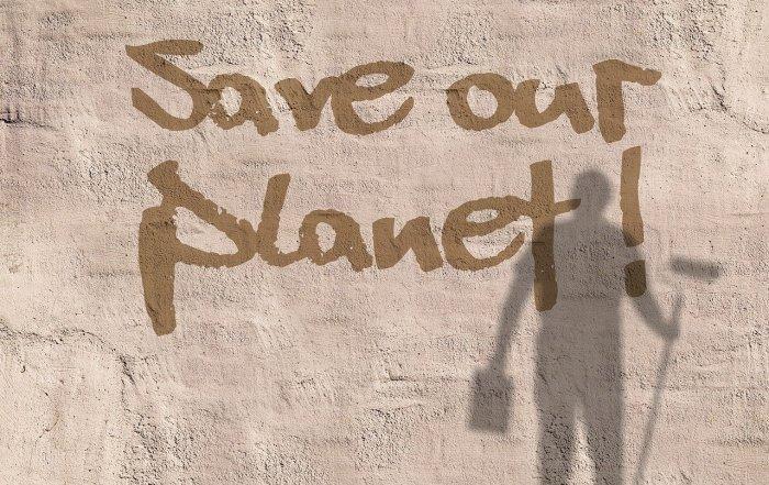 Schriftzug Save Our Planet auf einer Hauswand mit Schatten eines Malers