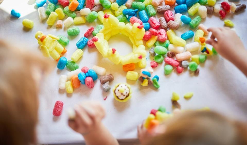 Bunte Bastelflips von Playmais liegen auf einem weißen Tisch, an dem zwei Kinder sitzen und eine kleine Krone aus gelben Maisflips basteln.