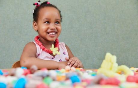 Ein junges Mädchen im Alter von etwa vier Jahren hat sich eine Kette aus roten und gelben Bastelflips gestaltet und freut sich darüber.