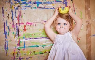 Ein junges Mädchen, etwa im Alter von zwei Jahren, steht vor einer bunt bemalten Wand und setzt sich wie eine Prinzessin ein selbstgebasteltes Krönchen aus PlayMais auf.
