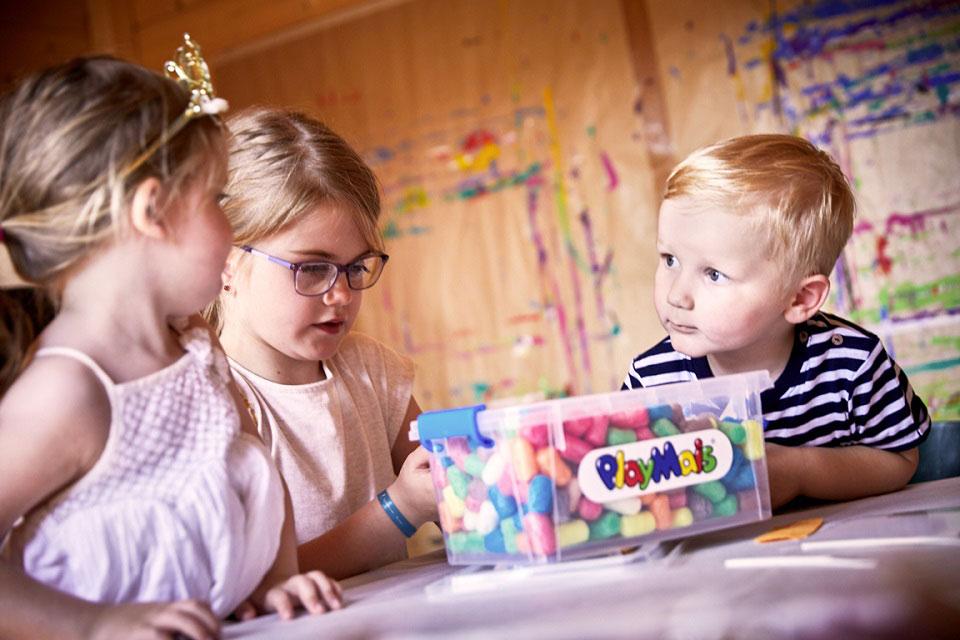 In einem Raum mit bunt bemalten Wänden sitzen drei Kinder an einem Tisch und basteln spielerisch mit den bunten PlayMais-Flips.