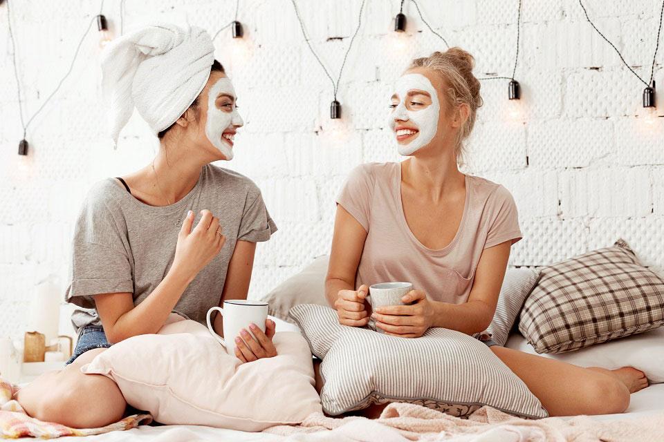 Zwei junge Mädchen sitzen auf einem Bett mit vielen Kissen und genießen ihen Beauty-Tag mit Gesichtsmaske und Haarkur.