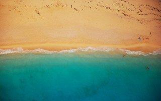Luftaufnahme zeigt leeren Strand und türkisblaue Brandung