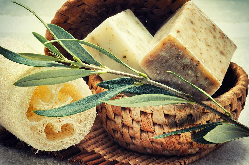 In einem geflochtenen Körbchen liegen zwei Stücke handgemachte Seife neben einem Luffa Schwamm und einem Olivenzweig.
