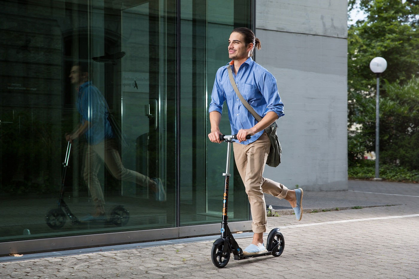 Tretroller für Erwachsene - ein junger Mann im Business-Look fährt ins Büro