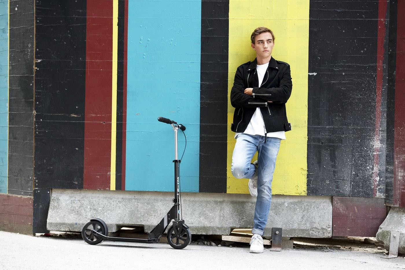 Tretroller für Erwachsene - ein junger mann steht mit Roller vor bunter Wand.