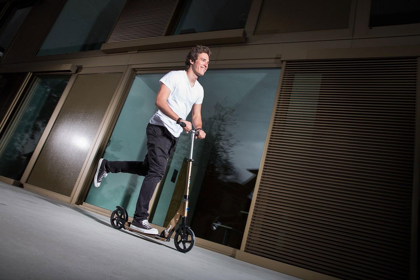 Trtroller für Erwachsene - Junger Mann fährt mit Micro Roller