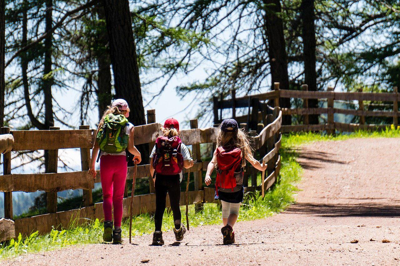 drei junge Mädchen mit Wanderausrüstung auf einem Wanderweg.