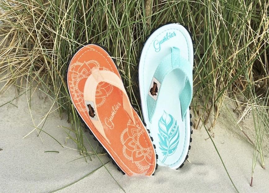 Je eine linke Zehensandale in Mint und eine in Coral liegen am Strand.