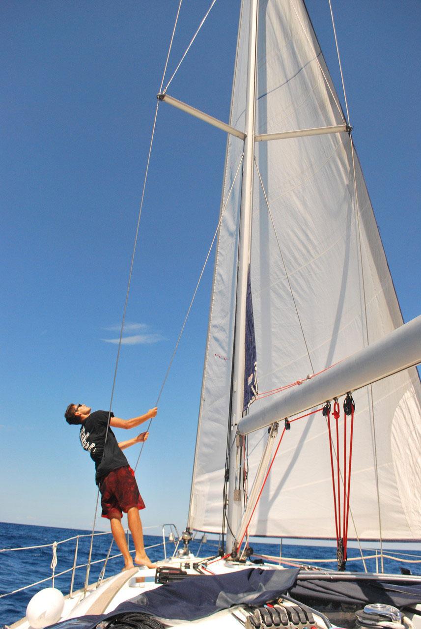 Mann hisst auf einer Yacht das Segel